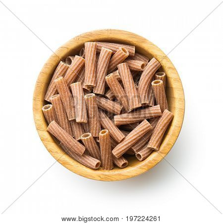 Dried rigatoni pasta in wooden bowl isolated on white background. Top view.