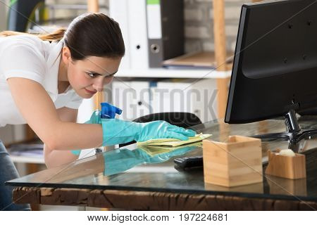 Happy Young Woman Cleaning The Glass Office Desk With Rag