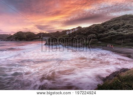 Editorial SWANSEA, UK - JULY 26, 2017: Rough seas at sunset on Caswell Bay, one of the most popular, easily accessible and closest beaches to Swansea City, on the Gower peninsula, South Wales, UK