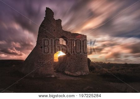 Dramatic sweeping psychedelic skies caught with a long exposure over Pennard castle on the Gower peninsula, Swansea.