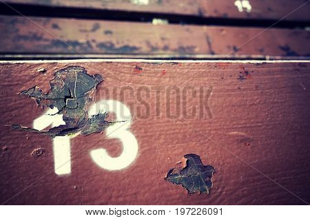Number Thirteen Painted On An Old Wooden Seat.