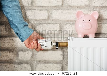 Woman's Hand Adjusting Temperature Of Radiator With Piggy Bank