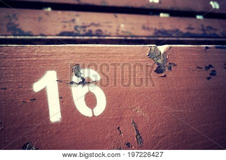 Number Sixteen Painted On An Old Wooden Seat.