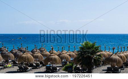 Hut umbrellas on the beach, sea on background, Tenerife, Spain