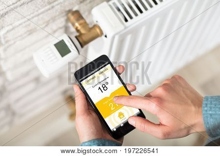 Close-up Of A Person's Hand Adjusting Temperature On Thermostat Through Cell Phone