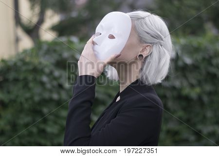 Young blond woman taking off a mask. Pretending to be someone else concept. outdoors