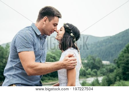 man with woman standing on the bridge across the river in mountains and kissing each other