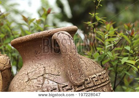 Antique cracked amphora in the garden on green background