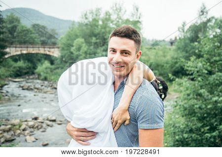 man taking woman in white dress on his shoulder near mountains river