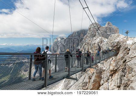 DACHSTEIN MOUNTAINS AUSTRIA - JULY 17 2017: Dachstein Mountain in Austria with hikers passing a skywalk rope bridge