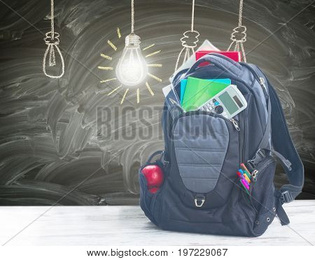 School backpack full of supplies on white desktop, blackboard with drawn idea lamps in background