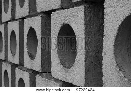 Illusory wall made of big gray bricks by bricklayer. Picture plays with light black and white. Creating abstract point of view.