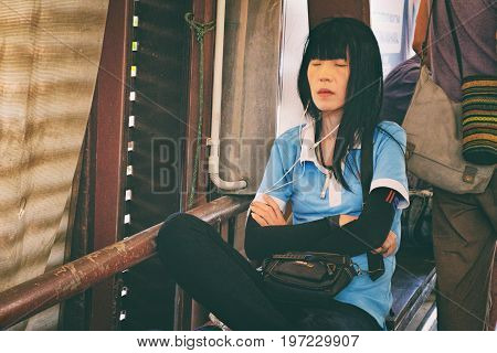 Bangkok, Thailand - January 9, 2016: Thai woman sitting on a bench of Chao Phraya Express Boat and sleeping lightly waiting for arrival