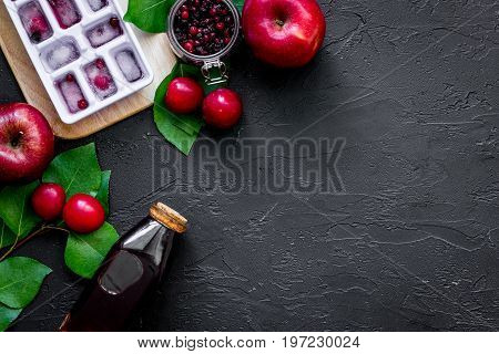 Summer ice fruit drink with apple, pulm and cranberry on black table top view.