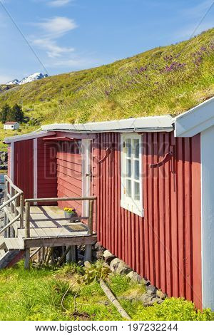 Part Of Red Classic Norwegian Rorbu fishing hut with sod roof on Lofoten islands, Norwegian traditional type of house used by fishermen