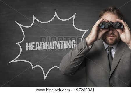 Businessman looking through binoculars by headhunting text on blackboard