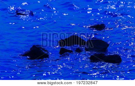 black stones in deep blue water; reflections on the water