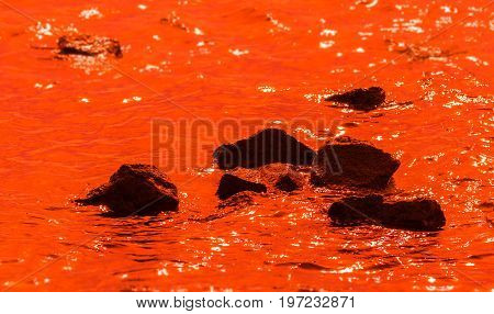 black stones in deep orange water; reflections on the water