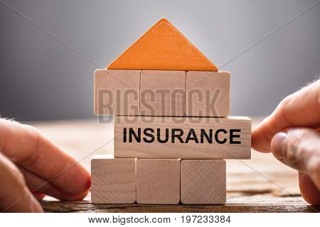 Closeup of hands building house model with insurance block on wood