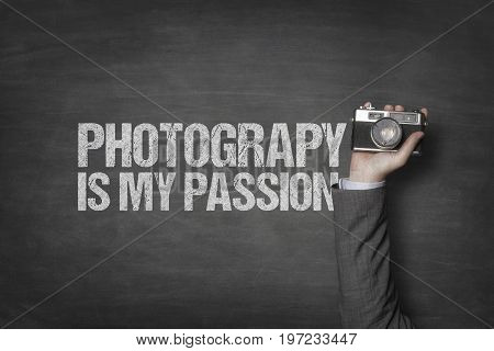 Cropped image of businessman's hand holding retro camera by photography is my passion text on blackboard