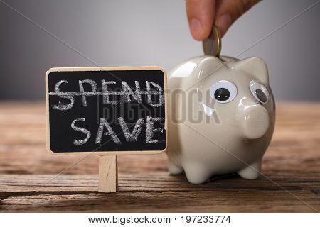 Closeup of hand putting coin in piggybank on wood representing saving plan