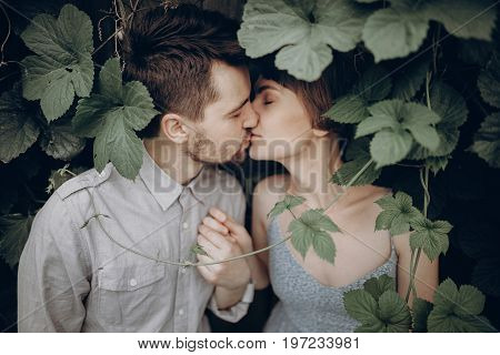 Stylish Hipster Couple Kissing In Green Leaves, Holding Hands. Man And Woman Embracing, In Love Rela
