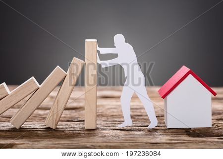 Closeup of paper man stopping wooden domino blocks by model home on table