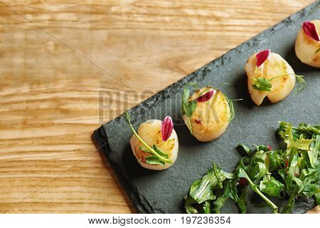 Slate plate with delicious scallops on table