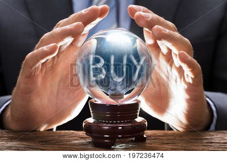 Midsection of businessman covering crystal ball with smoke forming buy text at wooden table