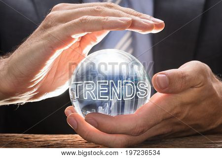 Midsection of businessman covering crystal ball with trends text and graphs at table
