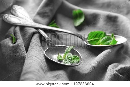 Spoons with fresh lemon balm leaves on fabric