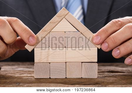 Midsection of businessman making model house with wooden blocks at table