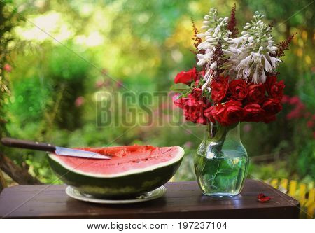 water melon cut with knife and roses flowers in vase on green summer garden background