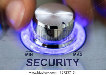 Cropped image of hand turning metallic illuminated knob by security text