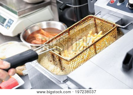 Female chef preparing french fries in kitchen