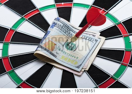 Closeup of arrow in papernotes on dartboard at table against black background