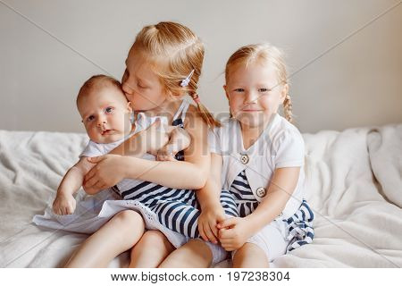 Lifestyle portrait of cute white Caucasian girls sisters holding kissing little baby sitting on bed indoors. Older siblings with younger brother sister newborn. Family love bonding together concept.