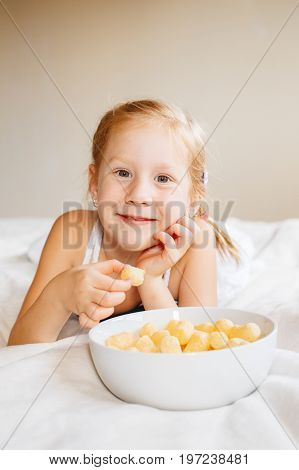 Portrait of one white Caucasian child girl smiling eating corn puffs. Preschooler kid eating snack fast food in bed at home indoors. Healthy meal childhood concept.