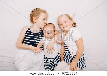 Lifestyle portrait of cute white Caucasian girls sisters holding kissing little baby lying on bed indoors. Older siblings with younger brother sister newborn. Family love bonding together concept.