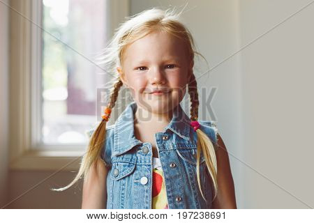 Closeup portrait of cute adorable white blonde Caucasian smiling girl looking in camera. Child girl with light fair hair with plaits wearing country village outfit jeans vest. Toned with filters.
