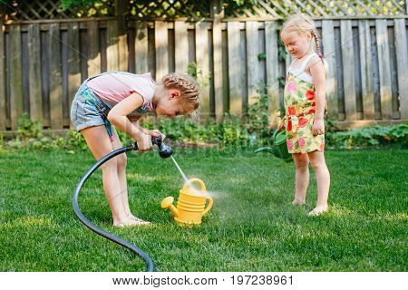 Portrait of two little girls sisters filling watering pot with water from gardening house on backyard on summer day. Lifestyle family activity. Kids responsibility for doing home chores.