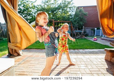 Portrait of two little girls sisters having fun on home backyard. Friends girls making silly faces. Lifestyle family moment of siblings playing together. Real authentic moment.