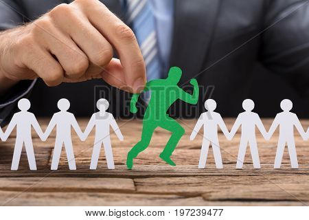 Midsection of businessman holding green paperman running amidst team on table