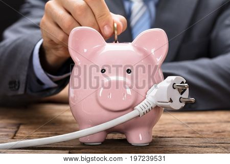 Midsection of businessman putting coin in piggybank with electric plug at wooden table