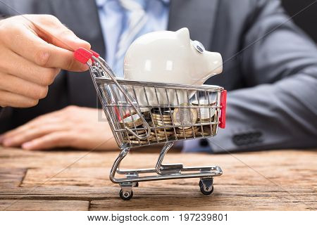 Midsection of businessman pushing piggybank and coins in shopping cart on wooden table