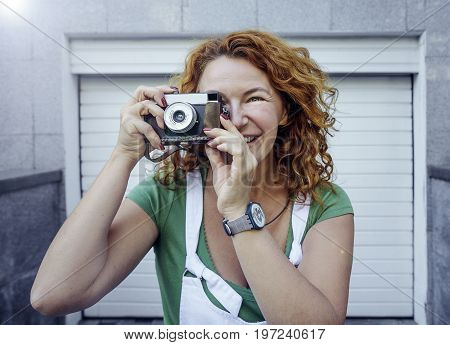 Red hair woman dressed in green shirt and white jacket smiling taking a photoshot on retro film camera, white pattern background