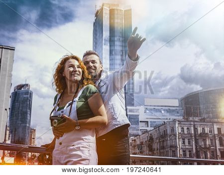 Middle aged man and woman having fun using an old film camera, on the background of city view. Man pointing by his hand