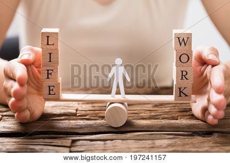 Close-up Of A Human Hand Protecting Balance Between Life And Work On Seesaw