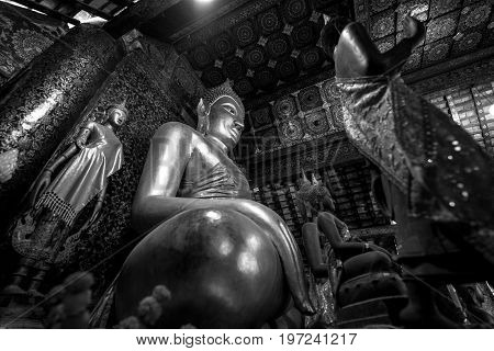 Black and white picture of sitting Buddha and other images inside Wat Xieng Thong Buddhist temple located in the city Luang Prabang Laos
