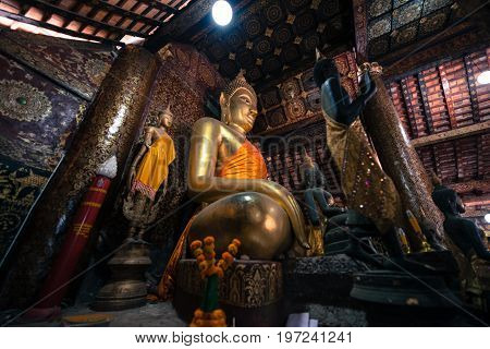 Wide angle picture of sitting Buddha and other images inside Wat Xieng Thong Buddhist temple located in the city Luang Prabang Laos